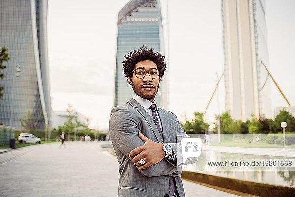 Porträt eines Geschäftsmannes mit Brille und grauem Anzug  der in die Kamera schaut.