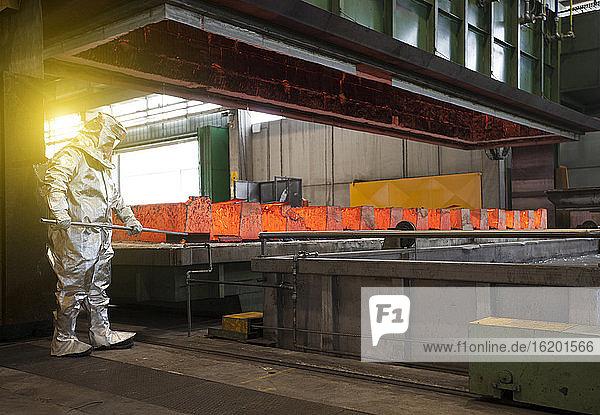 Mann in silbernem Hitzeschutzanzug  der in einem Stahlwerk arbeitet.