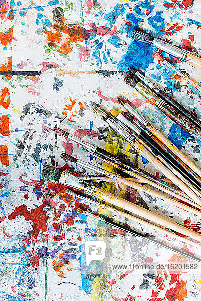 Still life of paintbrushes on colourful painted surface  overhead view
