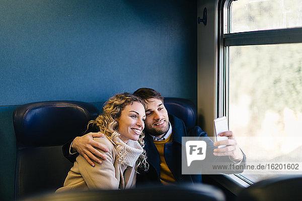 Couple taking selfie inside train