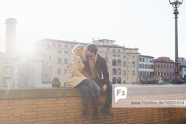 Pärchen küsst sich auf Ziegelsteinmauer  Florenz  Toskana  Italien