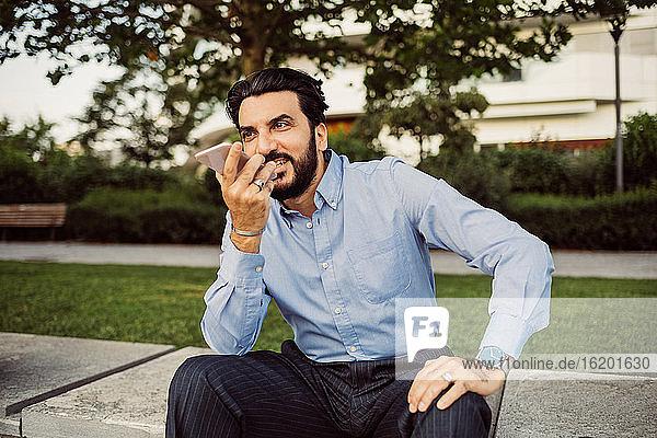 Portrait of bearded businessman wearing blue shirt  using mobile phone.