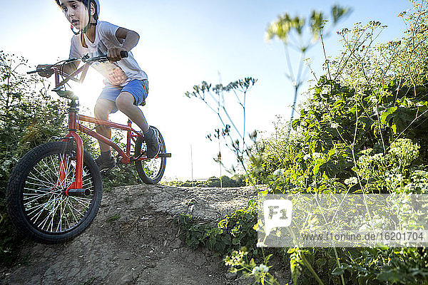 Boy riding down slope on a red BMX bicycle.