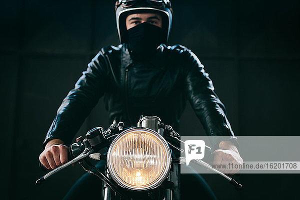 Junger männlicher Motorradfahrer auf einem Oldtimer-Motorrad in der Garage  Porträt