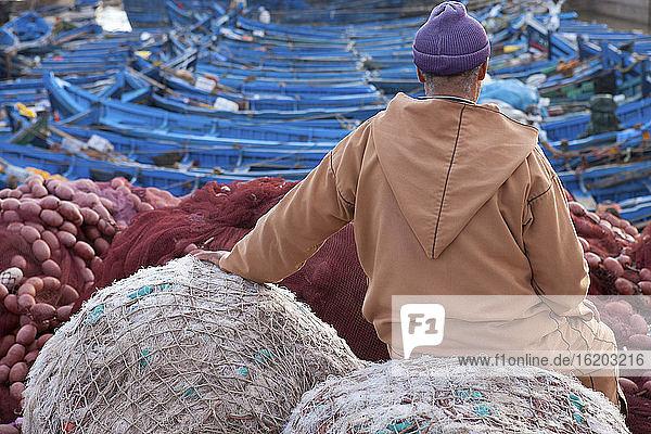 Local man sitting at fishing port  rear view  Essauira  Morocco