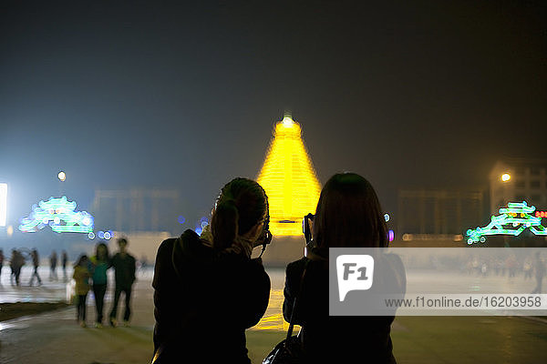 Two Chinese tourists taking photos of the illuminated pagoda in the centre of Sanjiang  Guangxi Provence  China