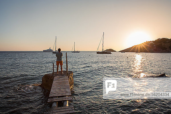 Young man looking out at sunset from old pier,  Ibiza,  Spain