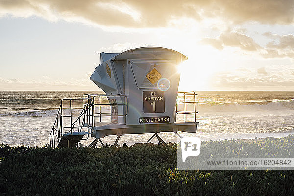 Lifeguard tower by ocean at sunset