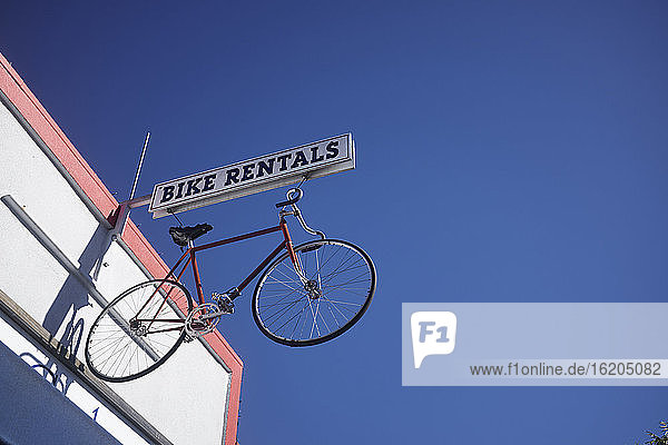 Bicycle sign for bike rental against blue sky  California  USA