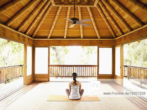 Rückansicht einer Frau  die in Lotus-Position auf dem Boden einer Yoga- und Meditationspagode in einem Luxusresort sitzt