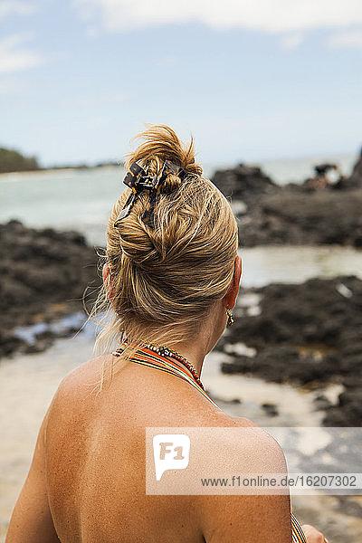 Rückansicht einer Frau an einem Strand mit Blick auf Felsen