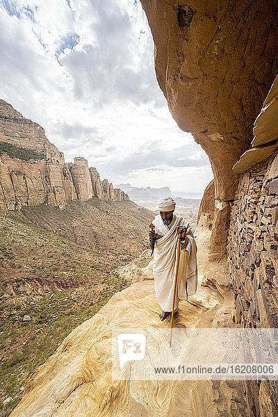 Priester hält das Handkreuz auf Felsen vor der Kirche von Abuna Yemata Guh  Gheralta-Gebirge  Region Tigray  Äthiopien  Afrika