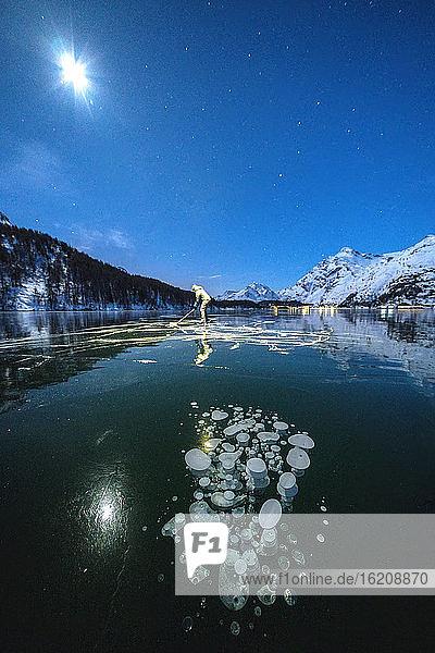 Vollmond auf Schlittschuhläufern auf dem gefrorenen Silsersee bei Stirnlampenlicht  Engadin  Kanton Graubünden  Schweiz  Europa