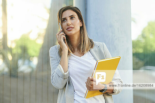 Businesswoman looking away while talking on mobile phone