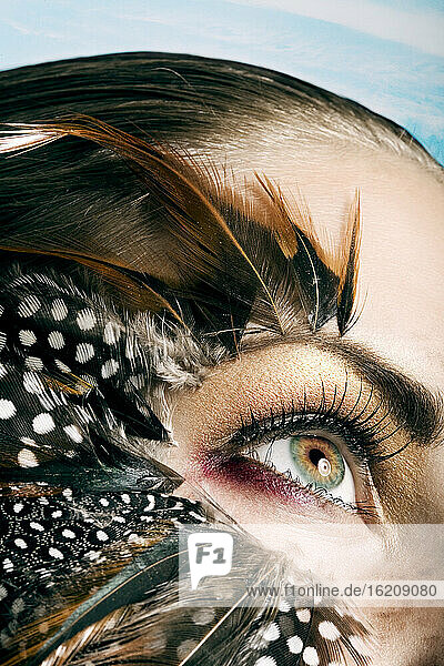 Young woman with Feathers around her eyes