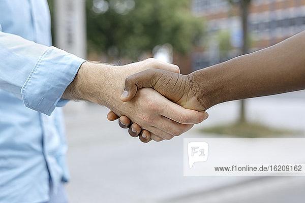 Freunde schütteln sich in der Stadt die Hände
