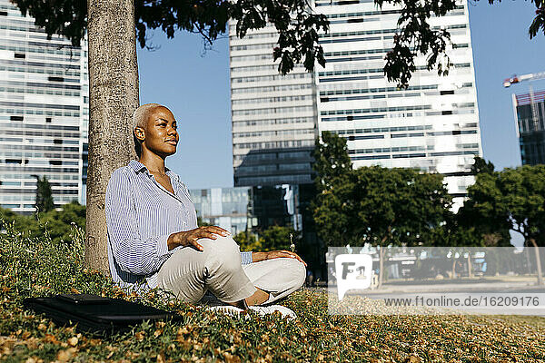 Smiling businesswoman sitting against tree trunk in city