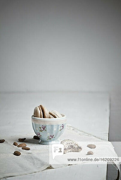 Bowl with macaroons while almonds scattered
