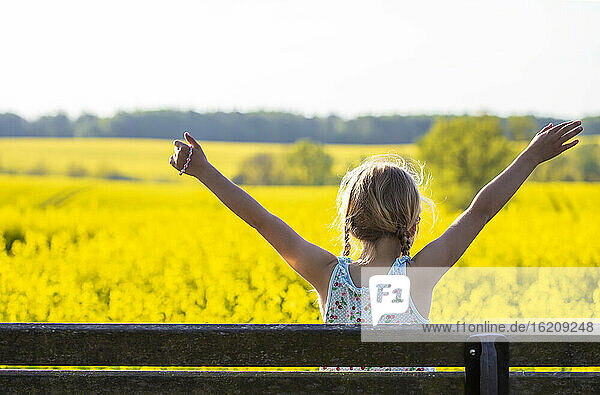 Girl with arms raised sitting in rapeseed field