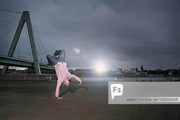 Germany  Cologne  Young man performing breakdance  Rhine bridge in background