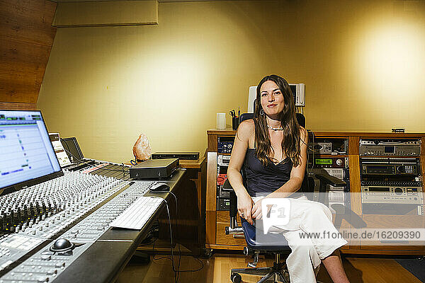Smiling female singer sitting in recording studio
