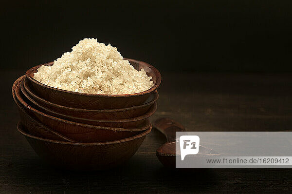 Bowl of sea salt on wooden table  close up