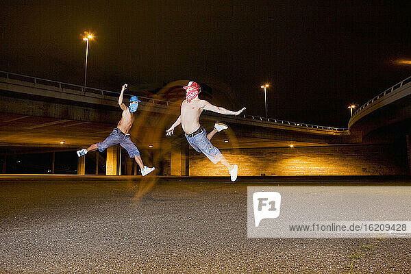 Germany  Cologne  Young people jumping  bridge in background