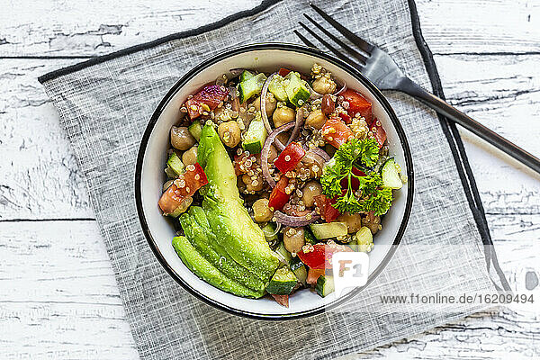 Bowl of vegetarian quinoa salad with chick-peas  avocado  cucumber  tomato  onion and parsley