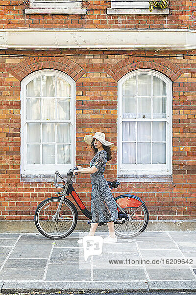 Young woman wearing hat with bicycle standing on street in city