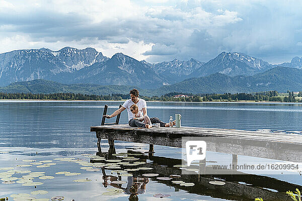 Father with daughter sitting on jetty over lake against mountains