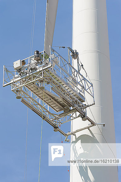 Germany  Saxony  Maintenance lift of wind turbine against sky