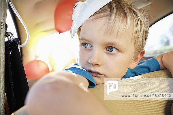 Deutschland  Nordrhein-Westfalen  Köln  Junge im Auto mit Osterhasenmaske  schaut weg