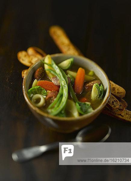 Schüssel mit Suppe  Wurst  Brotstangen und Gemüse auf Holztisch  Nahaufnahme