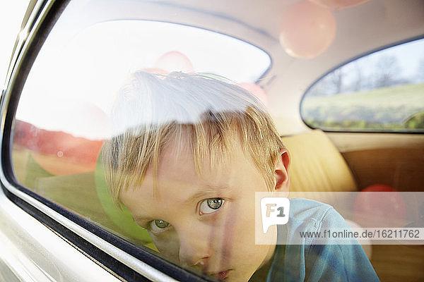 Deutschland  Nordrhein-Westfalen  Junge im Auto schaut durch Fenster