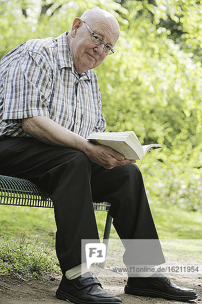 Germany  Cologne  Portrait of senior man reading book on park bench