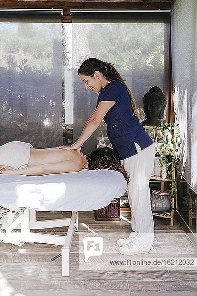 Therapist giving back massage to woman relaxing on table in health spa