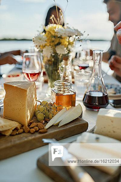 Käseplatte auf einem Tisch mit Menschen im Hintergrund Käseplatte auf einem Tisch mit Menschen im Hintergrund