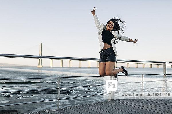 Junge Frau springt am Ufer