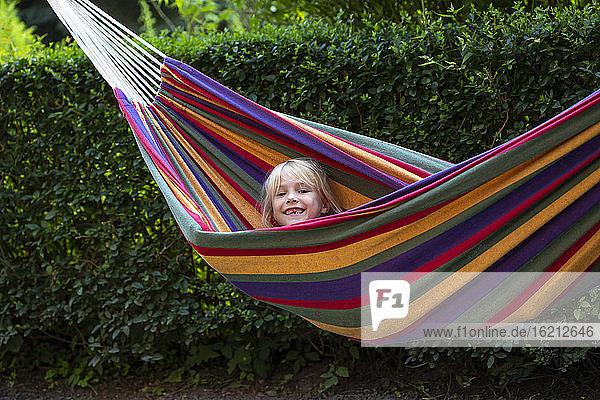 Cute girl enjoying while lying in hammock at garden