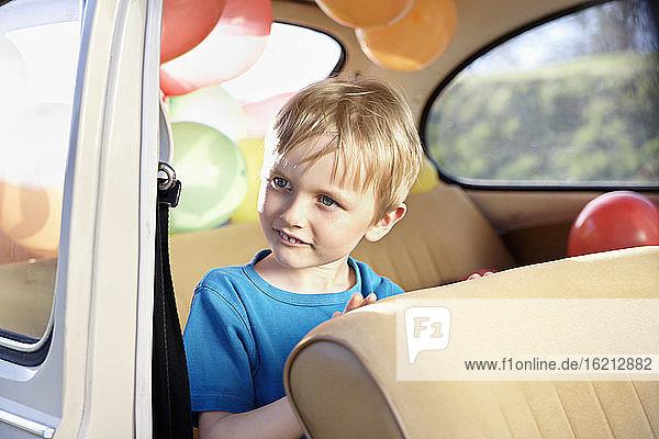 Deutschland  Nordrhein-Westfalen  Köln  Junge sitzt im Auto und schaut weg