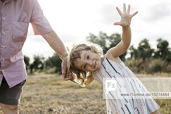 Cheerful cute girl holding grandfather's hand while standing on land against sky
