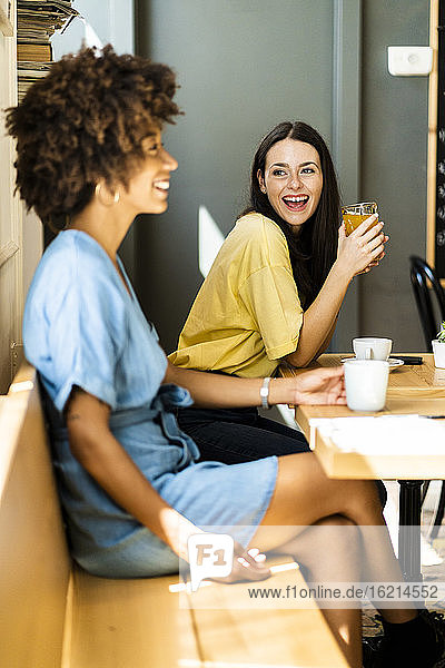 Cheerful woman holding drink while looking friend in cafe