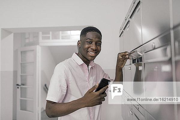 Lächelnder Mann mit Smartphone am Briefkasten