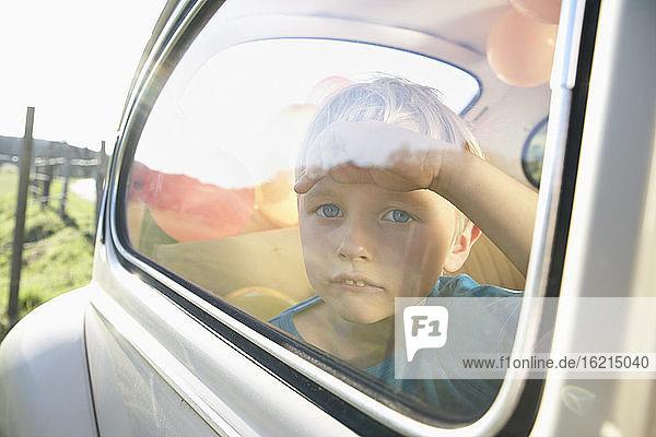 Deutschland  Nordrhein-Westfalen  Köln  Junge im Auto schaut durch Fenster