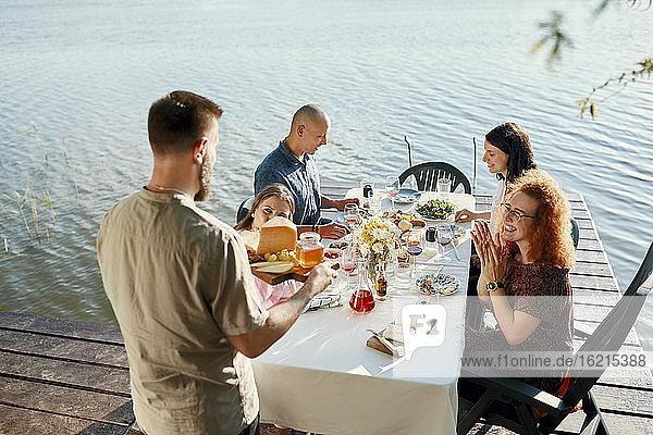 Freunde beim Abendessen an einem See mit einem Mann  der eine Käseplatte serviert Freunde beim Abendessen an einem See mit einem Mann, der eine Käseplatte serviert