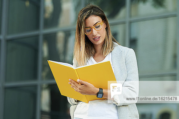 Businesswoman writing in notebook against office building