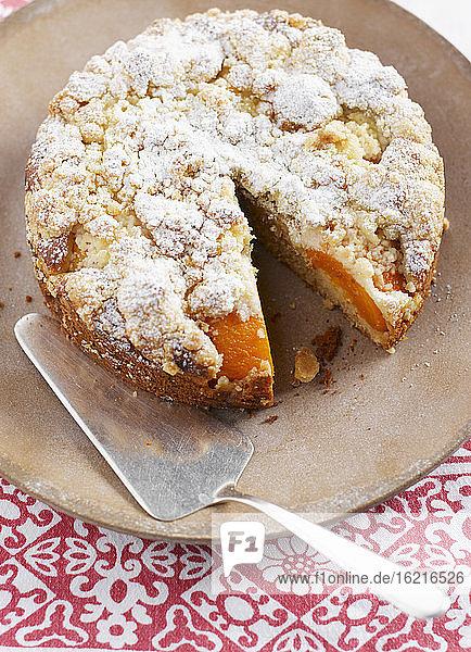 Pfirsich-Streuselkuchen mit Tortenheber auf Schneidebrett  Nahaufnahme