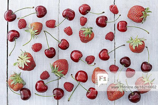 Kirschen und Erdbeeren auf Holztisch  Nahaufnahme