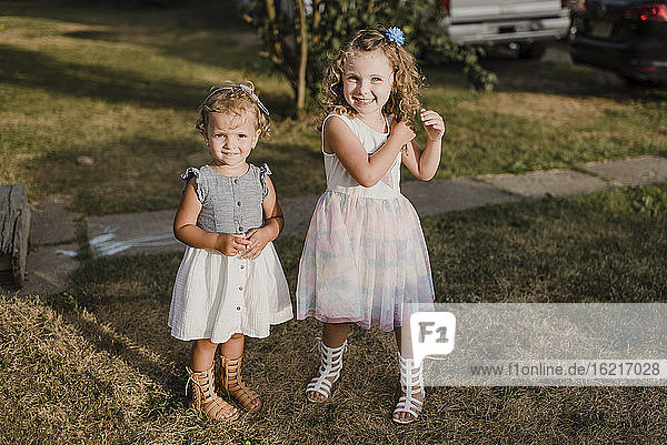 Portrait of two cute sisters standing on a meadow