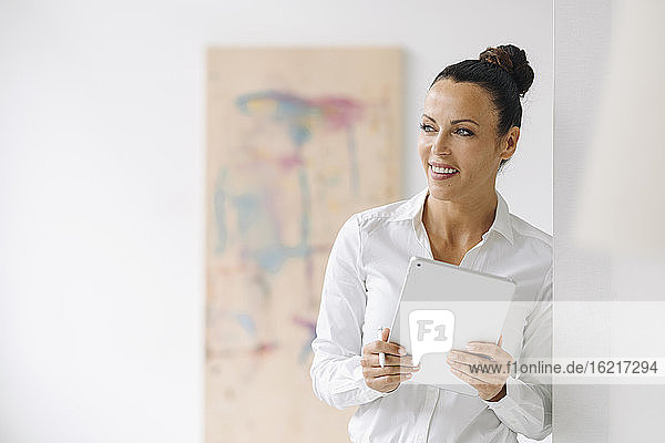 Smiling businesswoman holding digital tablet looking away while standing by wall in home office